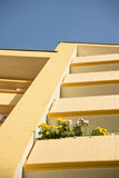Blommor på en balkong av en gul byggnad arkivbild
