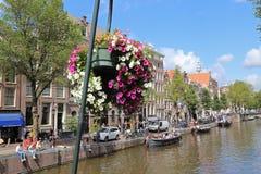 Blommor på en kanal med fartyg i Amsterdam, Holland Royaltyfria Bilder