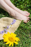 Blommor på ljus - gul pappers- hatt och ett par av ben Arkivbild