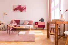 Blommor på trätabellen i rosa lägenhetinre med soffan under affischen bredvid kabinettet Verkligt foto arkivbilder