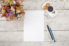 Blommor, pennor, blyertspennor, vitt ark av papper och kaffe Royaltyfri Bild