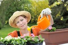 blommor som bevattnar kvinnabarn arkivbilder
