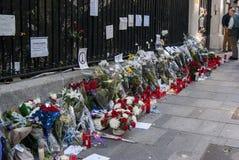 Blommor, stearinljus och tecknet mot terroristattack i Paris, förlade framme av fransk ambassad i Madrid, Spanien Arkivbilder