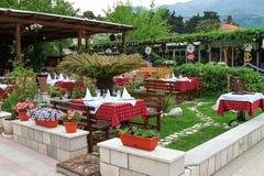 Blommor, tabeller och stolar i utomhus- restaurang terrasserar Royaltyfri Foto