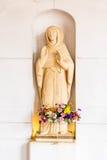 Blommor under statyn på kyrkan fotografering för bildbyråer