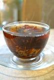 Blomningte i den genomskinliga koppen på det genomskinliga tefatet, ångan från det varma teet Arkivbilder