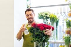 Blomsterhandlare eller säljare som ställer in röda rosor på blomsterhandeln royaltyfri foto
