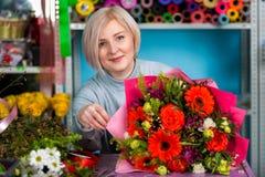 Blomsterhandlare i arbetsplatsen blommaillustrationen shoppar smellcomp Stående av en le kvinna Royaltyfria Foton