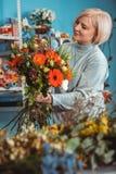 Blomsterhandlare i arbetsplatsen blommaillustrationen shoppar smellcomp Stående av en le kvinna Royaltyfria Bilder