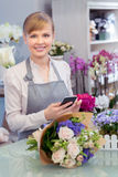 Blomsterhandlare med telefonen i henne händer arkivfoton
