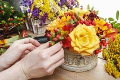 Blomsterhandlare på arbete: kvinnadanandebukett av orange rosor och hösten Arkivbilder