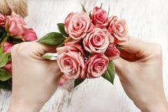 Blomsterhandlare på arbete Kvinnadanandebukett av rosa rosor Royaltyfri Fotografi