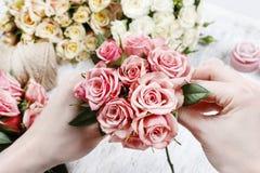 Blomsterhandlare på arbete Kvinnadanandebukett av rosa rosor Royaltyfria Bilder