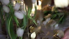 Blomsterhandlare på arbete Vita tulpan i klara Glass vaser, guld- blommor på tabellen lager videofilmer