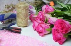 Blomsterhandlare p? arbete: n?tt bukett f?r kvinnadanandesommar av rosor p? en funktionsduglig tabell Kraft papper, sax, kuvert f royaltyfri fotografi