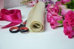 Blomsterhandlare p? arbete: n?tt bukett f?r kvinnadanandesommar av rosor p? en funktionsduglig tabell Kraft papper, sax, kuvert f royaltyfria bilder
