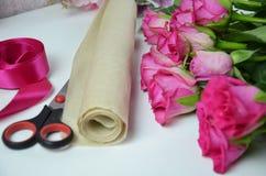 Blomsterhandlare p? arbete: n?tt bukett f?r kvinnadanandesommar av rosor p? en funktionsduglig tabell Kraft papper, sax, kuvert f arkivbilder