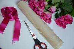 Blomsterhandlare p? arbete: n?tt bukett f?r kvinnadanandesommar av rosor p? en funktionsduglig tabell Kraft papper, sax, kuvert f royaltyfri bild