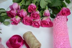 Blomsterhandlare p? arbete: n?tt bukett f?r kvinnadanandesommar av rosor p? en funktionsduglig tabell Kraft papper, sax, kuvert f arkivfoton