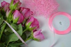 Blomsterhandlare p? arbete: n?tt bukett f?r kvinnadanandesommar av rosor p? en funktionsduglig tabell Kraft papper, sax, kuvert f royaltyfria foton