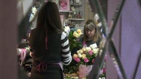 Blomsterhandlare skapar buketter i blomsterhandel stock video