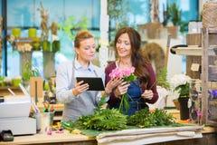 Blomsterhandlare som använder den Digital minnestavlan, medan göra buketten royaltyfri foto