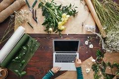 Blomsterhandlare som använder en bärbar dator royaltyfri bild