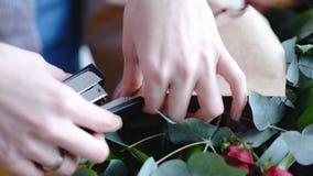 Blomsterhandlare som använder häftapparaten för att fästa ett hantverkpapper Övre sikt för slut av att ordna buketten royaltyfri foto