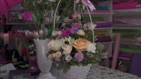 Blomsterhandlare som förbereder buketten i presentaffär lager videofilmer
