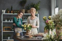 Blomsterhandlare som gör buketter arkivfoto