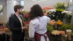 Blomsterhandlare som råder klientblommor för sammansättning arkivfilmer