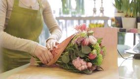 Blomsterhandlare som slår in blommor i papper på blomsterhandeln stock video