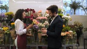 Blomsterhandlare som väljer blommor för bukett med klienten stock video