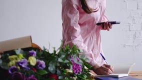 Blomsterhandlareanseendet på räknaren i blomsterhandel och att beräkna priset och skriver anmärkningar till notepaden stock video