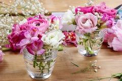 Blomsterhandlarearbetsplats: ofullständiga mycket små buketter i glass vaser Arkivbilder