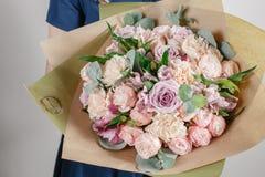 Blomsterhandlareflicka med richgruppblommor Ny fjäderbukett Blåtthav, Sky & moln Blomma för ung kvinna för födelsedag eller moder Arkivbild
