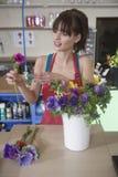Blomsterhandlaren Arranging Flower In shoppar Fotografering för Bildbyråer