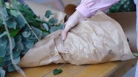 Blomsterhandlaren binder en bukett av stora blommor från kraft papper royaltyfria foton