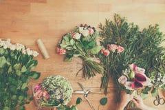 Blomsterhandlaren i blomsterhandelleverans gör den rosa buketten, bästa sikt för tabell royaltyfri fotografi