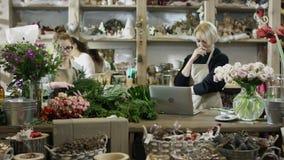 Blomsterhandlaren i svart tröja skrivar om något från en bärbar dator till en anteckningsbok, hennes kollega i exponeringsglas tr stock video