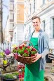 Blomsterhandlaren med blommakorgen på shoppar att sälja Royaltyfri Fotografi