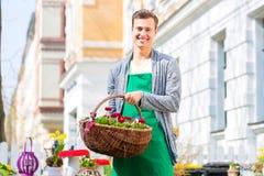 Blomsterhandlaren med blommakorgen på shoppar att sälja Arkivbilder