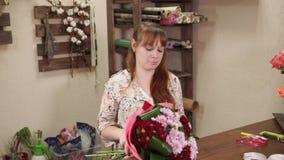 Blomsterhandlaren monterar den härliga buketten stock video