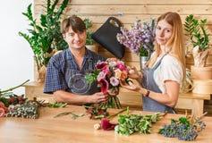 Blomsterhandlaren och assistenten i blomsterhandelleverans gör den rosa buketten Royaltyfri Foto