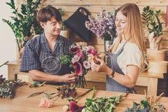 Blomsterhandlaren och assistenten i blomsterhandelleverans gör den rosa buketten Royaltyfria Bilder