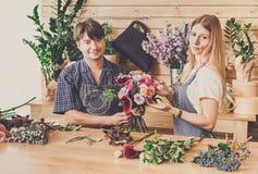 Blomsterhandlaren och assistenten i blomsterhandelleverans gör den rosa buketten Arkivbild