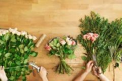 Blomsterhandlaren och assistenten i blomsterhandelleverans gör den rosa buketten, bästa sikt för tabell arkivfoton