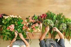Blomsterhandlaren och assistenten i blomsterhandelleverans gör den rosa buketten, bästa sikt för tabell royaltyfri bild