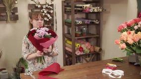 Blomsterhandlaren samlar blom- ordningar, en kvinna sätter ett ljust papper arkivfilmer