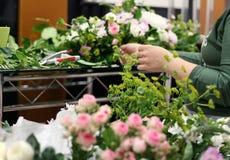 Blomsterhandlaren som skapar sammansättning från blommor Arkivfoto